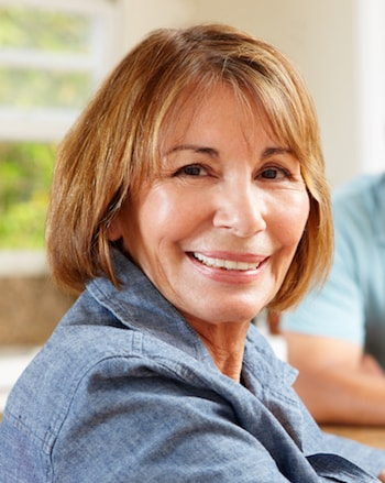 Smiling woman who needs a Dental Implants in Shelby Township denture