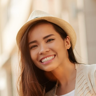 A girl wearing a hat and smiling due to General Dentistry in Shelby Township