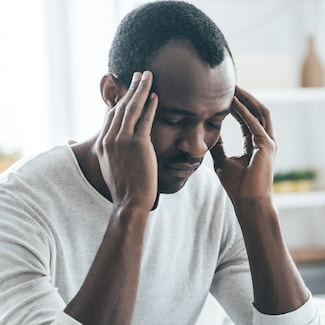 Man holding his head due to TMJ, which he can have treated with Shelby Township Cosmetic Dentistry