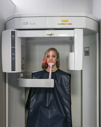 Woman standing in an i-CAT machine as part of Dental Implants in Shelby Township